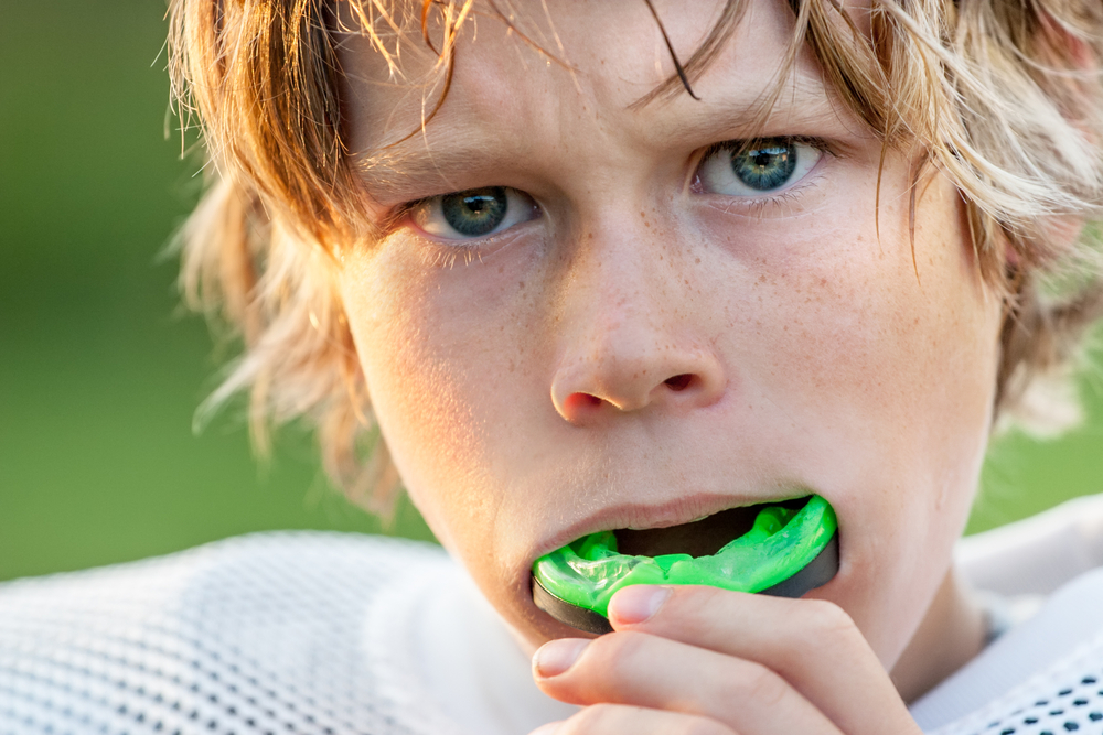 young boy foot ball player with athletic mouth guard he is pulling out of his mouth